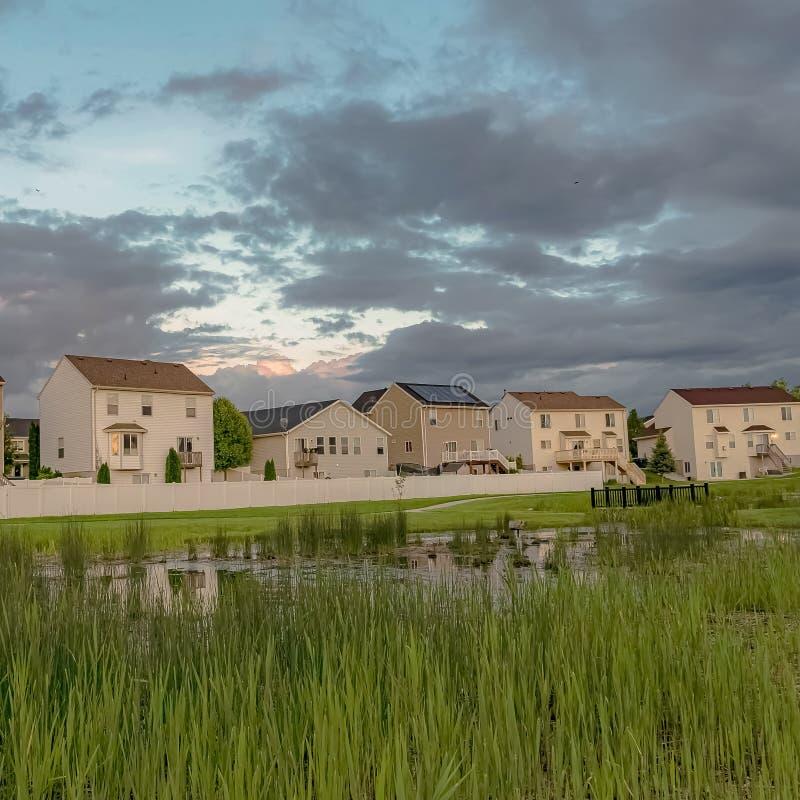 Τα τετραγωνικά σπίτια με τα μπαλκόνια και μια άποψη της χλοώδους λίμνης γεφυρώνουν και επεκτατικός πράσινος τομέας στοκ φωτογραφία με δικαίωμα ελεύθερης χρήσης
