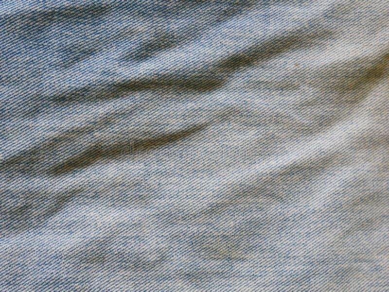 Τα τζιν στο μπλε πλυσίματος με σχίζουν Υπόβαθρο τζιν, σύσταση Σχισμένος Οργανικός, σχέδιο στοκ φωτογραφίες