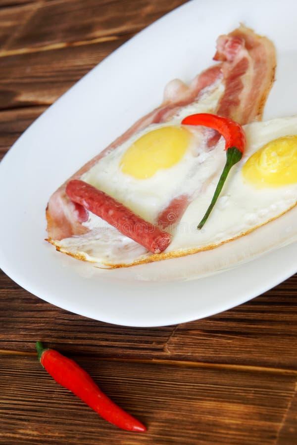 Τα τηγανισμένα αυγά με το μπέϊκον, το κόκκινο πιπέρι τσίλι και τα μικρά λουκάνικα βρίσκονται σε ένα άσπρο πιάτο σε μια φυσική ξύλ στοκ φωτογραφία με δικαίωμα ελεύθερης χρήσης
