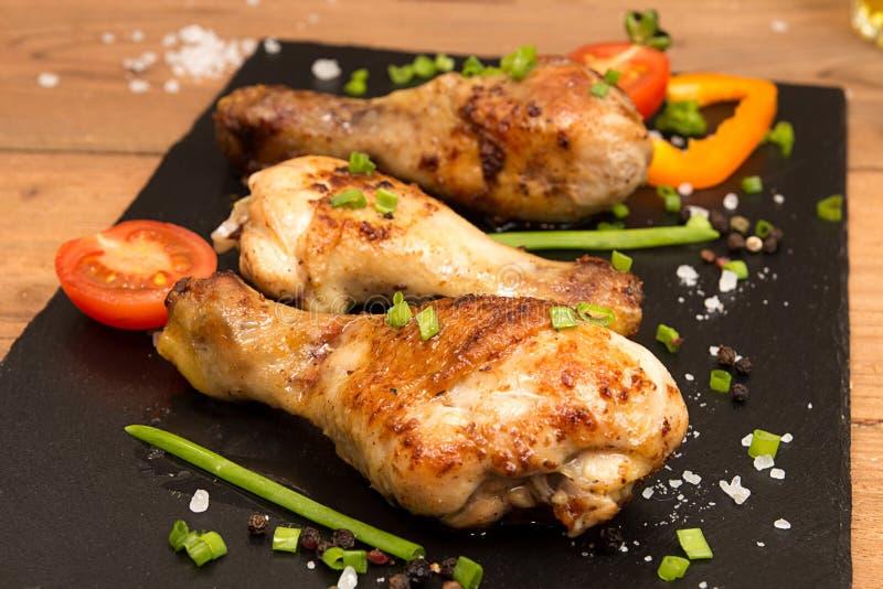 Τα τηγανισμένα πόδια κοτόπουλου διακοσμούν την ντομάτα και το δέσμη-κρεμμύδι κερασιών στοκ εικόνες