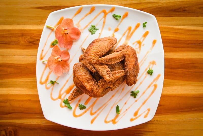 Τα τηγανισμένα φτερά κοτόπουλου εξυπηρέτησαν στο πιάτο με τη τοπ άποψη σάλτσας - πιάτο των τριζάτων φτερών κοτόπουλου στον ξύλινο στοκ φωτογραφία με δικαίωμα ελεύθερης χρήσης