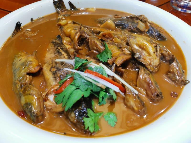 Τα τηγανισμένα ψάρια με το ζυμωνομμένο φασόλι κολλούν το κινεζικό πιάτο στοκ φωτογραφία