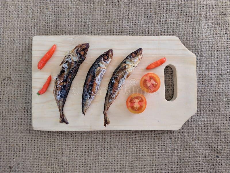 Τα τηγανισμένα ψάρια χτυπούν στον ξύλινο τέμνοντα πίνακα, που εξυπηρετείται με τα τσίλι και τις ντομάτες στοκ εικόνα με δικαίωμα ελεύθερης χρήσης