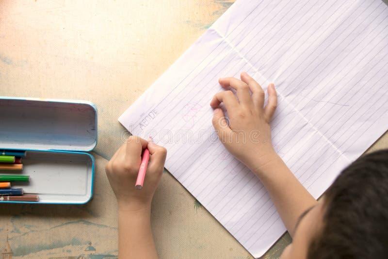 Τα τοπ παιδιά άποψης κρατούν ένα μολύβι και έναν σχεδιασμό χρώματος στοκ εικόνες