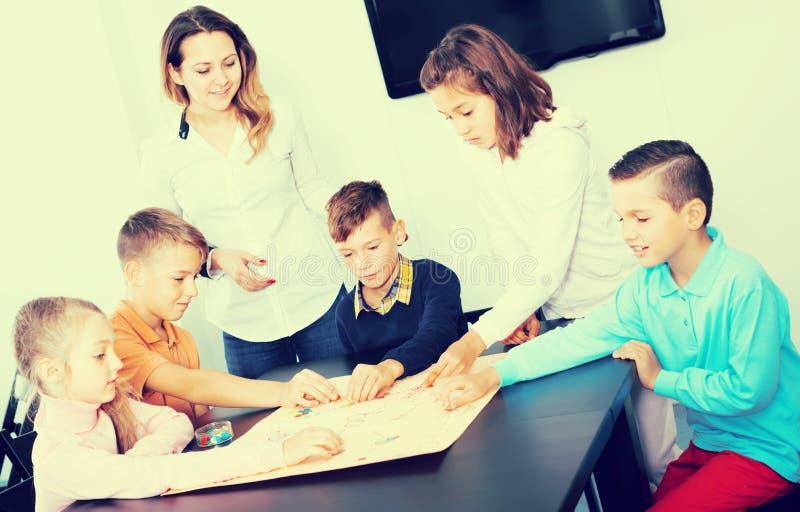 Τα του δημοτικού σχολείου παιδιά ηλικίας στον πίνακα με το επιτραπέζιο παιχνίδι και χωρίζουν σε τετράγωνα στοκ εικόνα