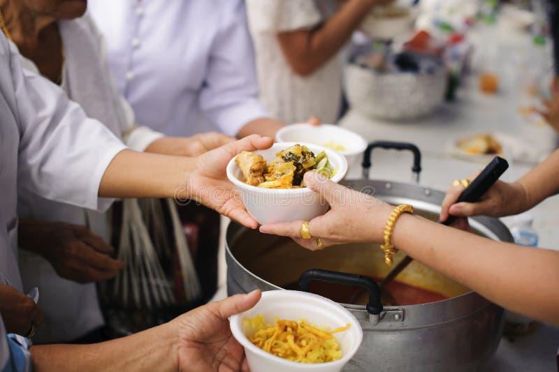 Τα τρόφιμα φιλανθρωπίας είναι ελεύθερα για τους ανθρώπους στις τρώγλες: Τα χέρια των εθελοντών εξυπηρετούν τα ελεύθερα τρόφιμα φτ στοκ εικόνες