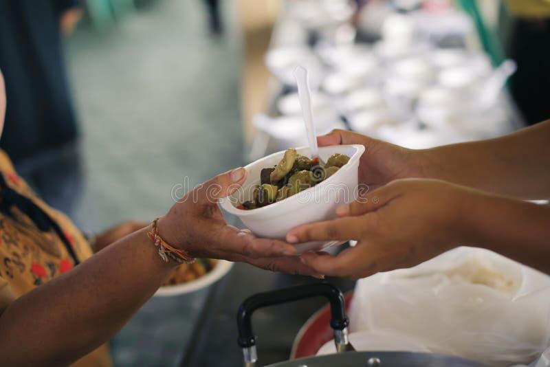 Τα τρόφιμα φιλανθρωπίας είναι ελεύθερα για τους ανθρώπους στις τρώγλες: Τα χέρια των εθελοντών εξυπηρετούν τα ελεύθερα τρόφιμα φτ στοκ φωτογραφίες με δικαίωμα ελεύθερης χρήσης