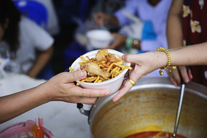 Τα τρόφιμα φιλανθρωπίας είναι ελεύθερα για τους ανθρώπους στις τρώγλες: Τα χέρια των εθελοντών εξυπηρετούν τα ελεύθερα τρόφιμα φτ στοκ εικόνα