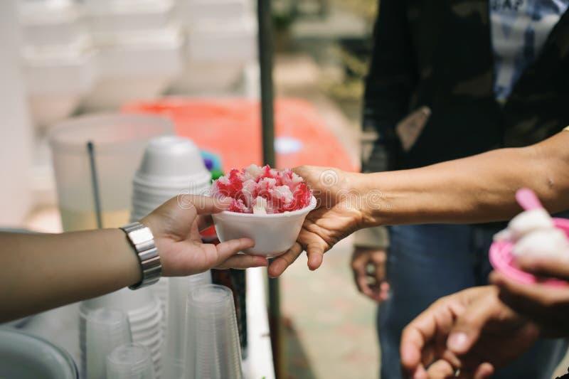 Τα τρόφιμα φιλανθρωπίας είναι ελεύθερα για τους ανθρώπους στις τρώγλες: Τα χέρια των εθελοντών εξυπηρετούν τα ελεύθερα τρόφιμα φτ στοκ φωτογραφία