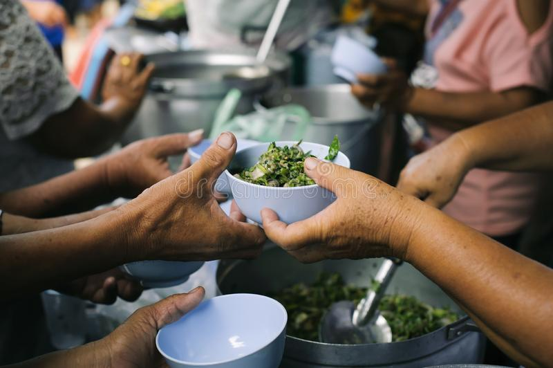 Τα τρόφιμα φιλανθρωπίας είναι ελεύθερα για τους ανθρώπους στις τρώγλες: Τα χέρια των εθελοντών εξυπηρετούν τα ελεύθερα τρόφιμα φτ στοκ εικόνα με δικαίωμα ελεύθερης χρήσης