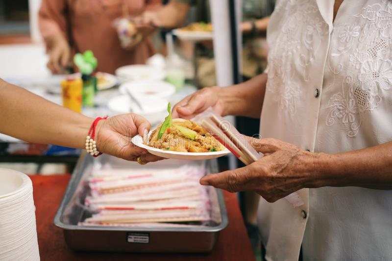 Τα τρόφιμα φιλανθρωπίας είναι ελεύθερα για τους ανθρώπους στις τρώγλες: Τα χέρια των εθελοντών εξυπηρετούν τα ελεύθερα τρόφιμα φτ στοκ εικόνες με δικαίωμα ελεύθερης χρήσης