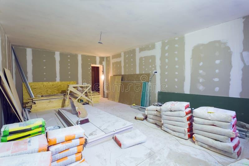 Τα υλικά για putty κατασκευής τα πακέτα, φύλλα της γυψοσανίδας ή του ξηρού τοίχου στο διαμέρισμα είναι κάτω από την κατασκευή στοκ εικόνα με δικαίωμα ελεύθερης χρήσης