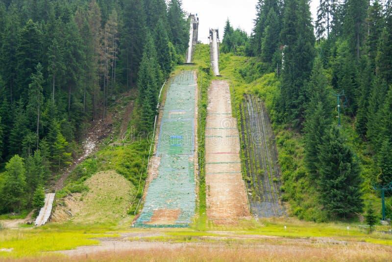 Τα υπολείμματα ενός σκι πηδούν σε έναν πράσινο λόφο στοκ φωτογραφίες