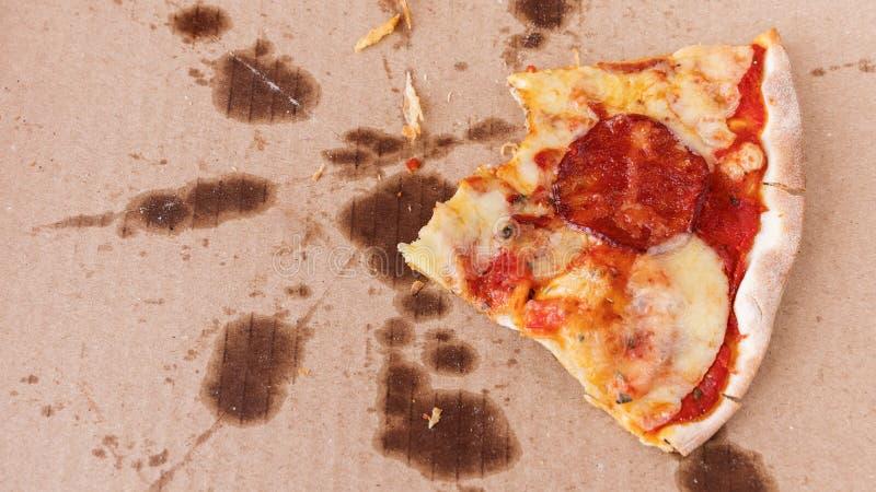 Τα υπολείμματα της μισό-?αγωμένης πίτσας σε ένα λιπαρό κιβώτιοφαγωμέν στοκ εικόνα