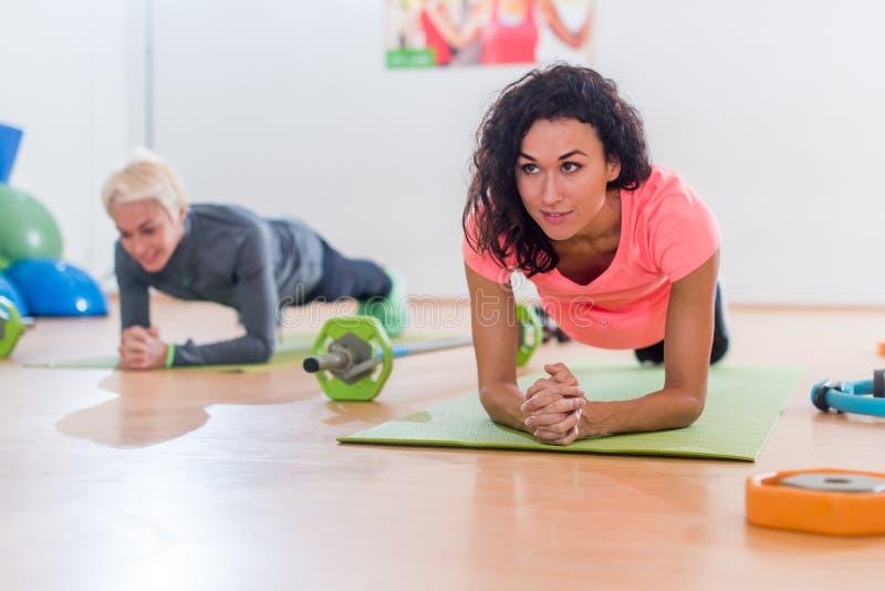 Τα φίλαθλα ελκυστικά νέα θηλυκά που κάνουν γιόγκας άσκηση ή το δελφίνι αντιβράχιων τη planking θέτουν στα χαλιά εκπαιδευτικά στην στοκ φωτογραφίες με δικαίωμα ελεύθερης χρήσης