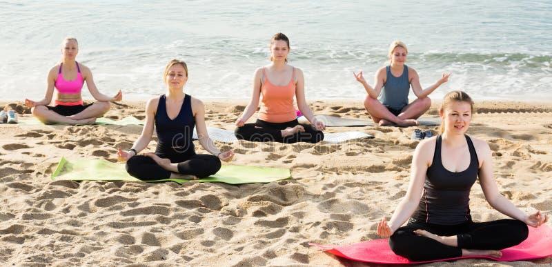 Τα φίλαθλα θηλυκά που στη γιόγκα τοποθετούν Padmasana στην παραλία στοκ εικόνα με δικαίωμα ελεύθερης χρήσης