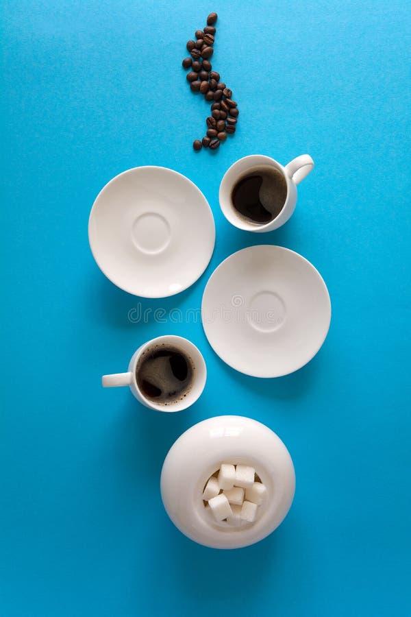 Τα φλυτζάνια με το espresso καταβρέχουν, πιατάκια, κουταλάκι του γλυκού και φασόλια καφέ στο μπλε υπόβαθρο εγγράφου Έννοια καλημέ στοκ φωτογραφία