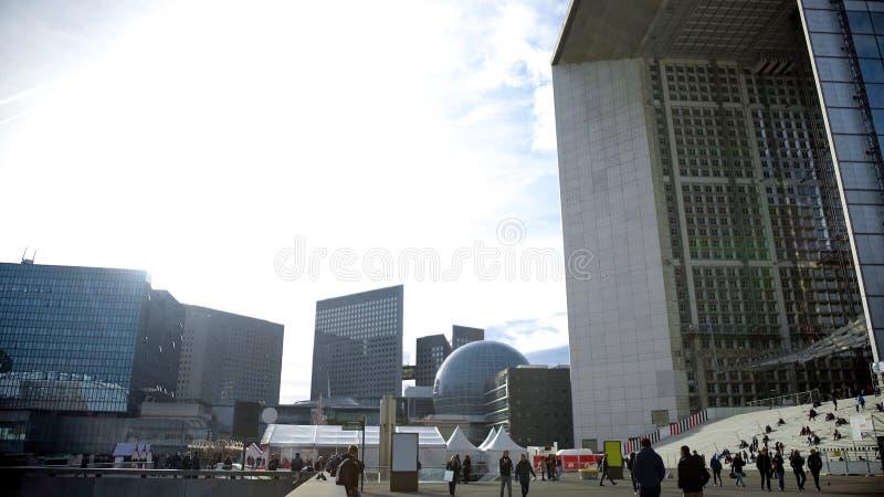 Τα φουτουριστικά κτήρια στο Παρίσι στρέφονται, άνθρωποι που περπατούν πέρα από την τετραγωνική, πολυάσχολη ζωή στοκ εικόνες