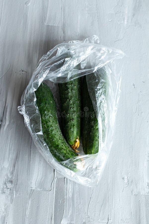 Τα φρέσκα αγγούρια που συσκευάζονται στη πλαστική τσάντα, επίπεδο τροφίμων βάζουν με το διάστημα για το κείμενο, οικολογική έννοι στοκ εικόνα
