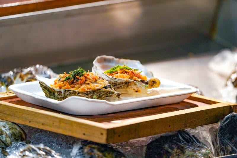 Τα φρέσκα ακατέργαστα μεγάλα στρείδια ζευγών στο πιάτο αφρού και το ξύλινο κάλυμμα πιάτων από το τηγανισμένο σκόρδο και βγάζουν φ στοκ εικόνες