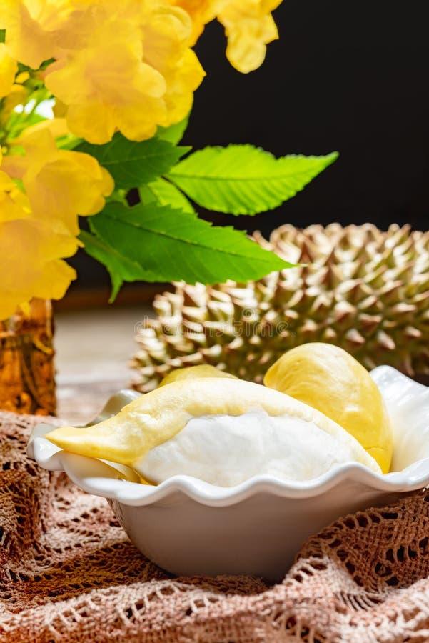 Τα φρέσκα κίτρινα durian φρούτα σε ένα κύπελλο και διακοσμούν με τα λουλούδια Γλυκιά έννοια επιδορπίων στοκ εικόνα