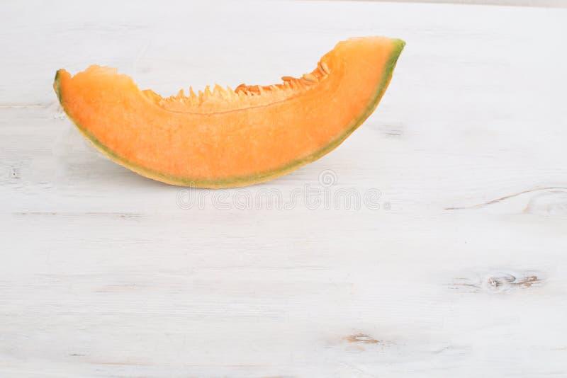 Τα φρέσκα οργανικά υγιή φρούτα έννοιας θερινών συγκομιδών τεμάχισαν το πεπόνι στο άσπρο ξύλινο υπόβαθρο στοκ φωτογραφία με δικαίωμα ελεύθερης χρήσης