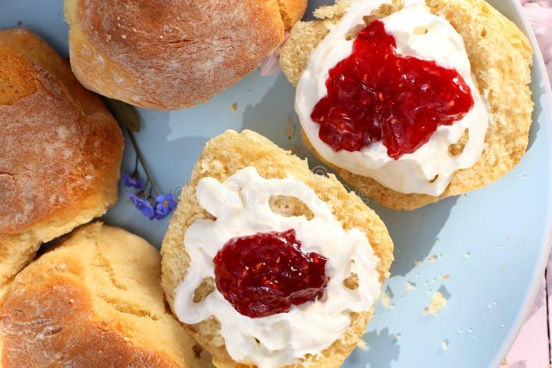 Τα φρέσκα σκωτσέζικα scones με την κρέμα και το σμέουρο φράσσουν κοντά επάνω στοκ εικόνες
