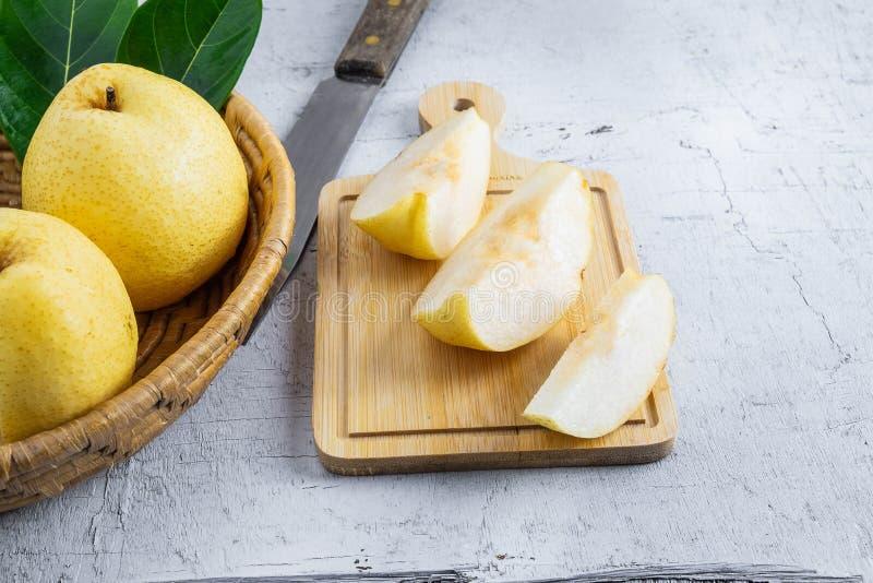 Τα φρέσκα φρούτα αχλαδιών nashi σε έναν άσπρο ξύλινο πίνακα έκοψαν ένα μισό στο α στοκ εικόνες με δικαίωμα ελεύθερης χρήσης