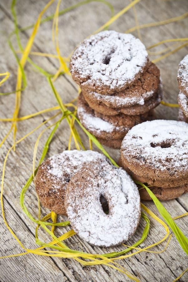 Τα φρέσκα ψημένα μπισκότα τσιπ σοκολάτας με τη ζάχαρη κονιοποιούν τους σωρούς στον ξύλινο πίνακα στοκ εικόνα με δικαίωμα ελεύθερης χρήσης