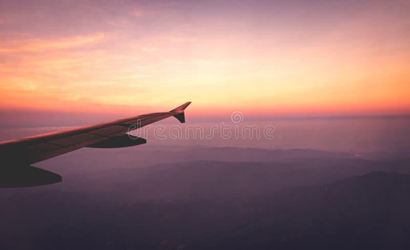 Τα φτερά αεροπλάνων στον ουρανό και βουνά βλέπουν τη σκηνή στην ανατολή Ταξίδι και περιπέτεια στοκ φωτογραφία με δικαίωμα ελεύθερης χρήσης