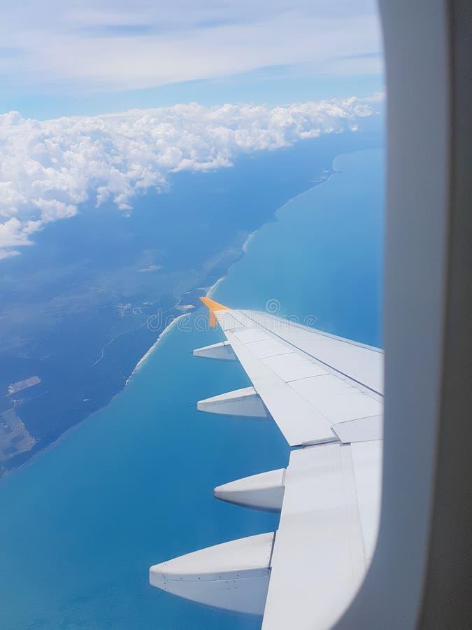 Τα φτερά του αεροπλάνου σε ένα υπόβαθρο σύννεφων και το φωτεινό ουρανό στοκ φωτογραφία με δικαίωμα ελεύθερης χρήσης