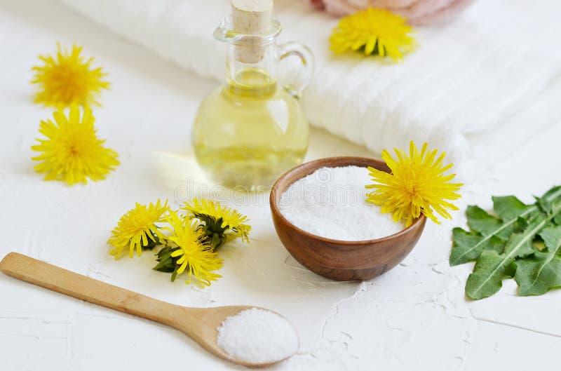 Τα φυσικά συστατικά για το σπιτικό άλας σωμάτων τρίβουν με τα λουλούδια πικραλίδων, το ελαιόλαδο λεμονιών, μελιού και στοκ φωτογραφία με δικαίωμα ελεύθερης χρήσης