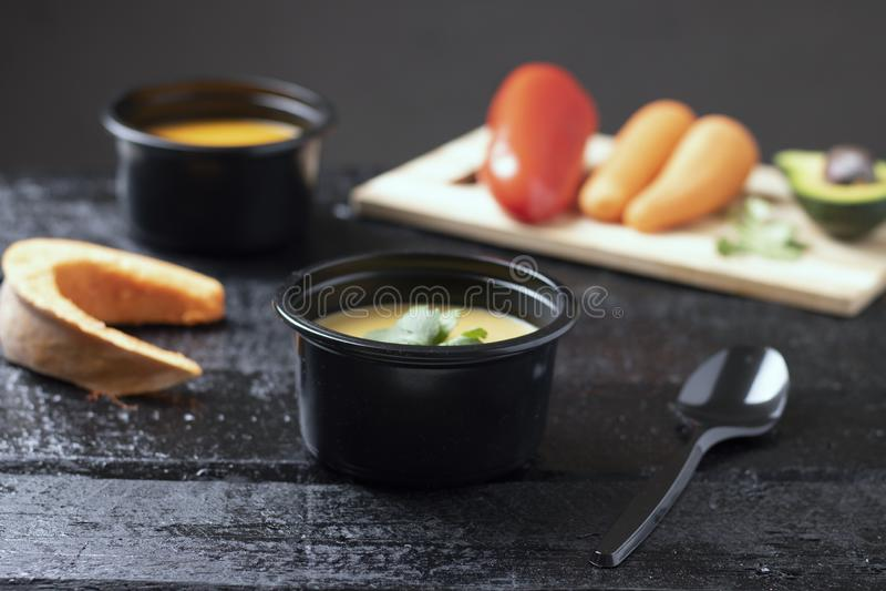 Τα φύλλα σούπας και μεντών κολοκύθας, το κουάκερ κουταλιών, πιπεριών και μπιζελιών στο εμπορευματοκιβώτιο τροφίμων στον ξύλινο πί στοκ εικόνες
