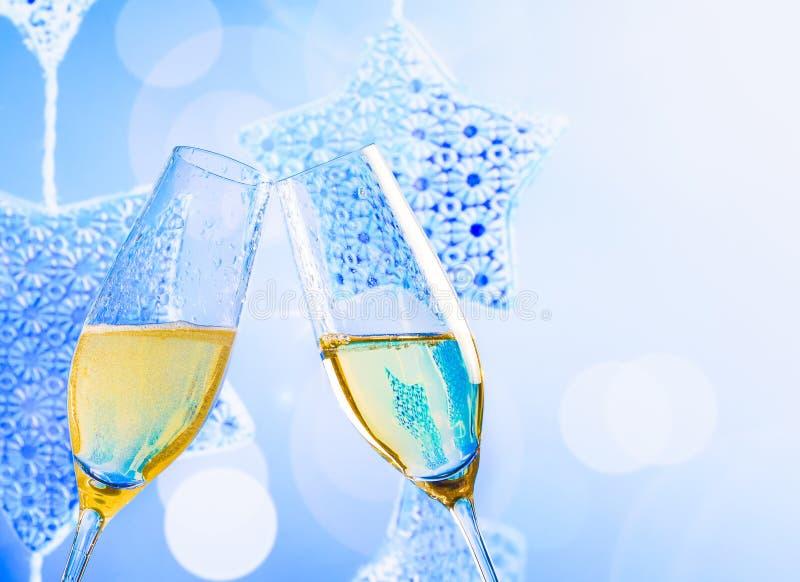 Τα φλάουτα CHAMPAGNE με τις χρυσές φυσαλίδες στα μπλε Χριστούγεννα ανάβουν το υπόβαθρο διακοσμήσεων στοκ φωτογραφία με δικαίωμα ελεύθερης χρήσης