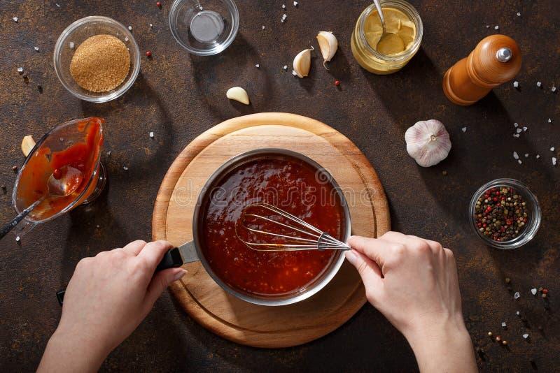 Τα χέρια αναμιγνύουν τη bbq σάλτσα με χτυπούν ελαφρά στην κατσαρόλλα στοκ εικόνες
