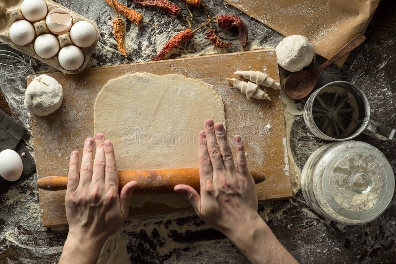 Τα χέρια αρχιμαγείρων κυλούν τη ζύμη στοκ εικόνα