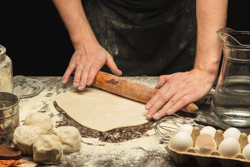 Τα χέρια αρχιμαγείρων κυλούν τη ζύμη στοκ φωτογραφία με δικαίωμα ελεύθερης χρήσης