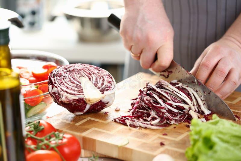 Τα χέρια αρχιμαγείρων που τεμαχίζουν το πορφυρό λάχανο σαλάτας διχοτομούν στοκ φωτογραφία με δικαίωμα ελεύθερης χρήσης
