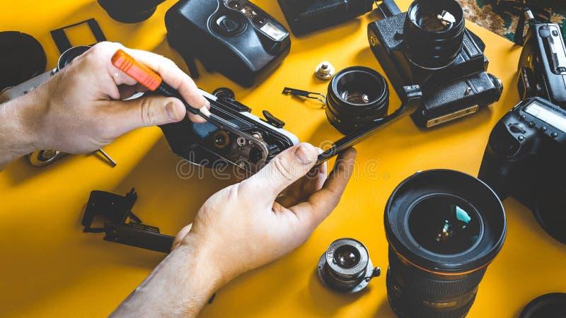 Τα χέρια ατόμων επισκευάζουν τη σπασμένη κάμερα ταινιών, εργασιακός χώρος φωτογραφιών στοκ εικόνα