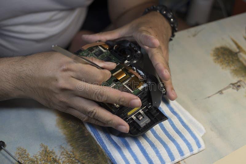 Τα χέρια ατόμων επισκευάζουν τη σπασμένη κάμερα ταινιών, εργασιακός χώρος φωτογραφιών Freela στοκ εικόνες με δικαίωμα ελεύθερης χρήσης