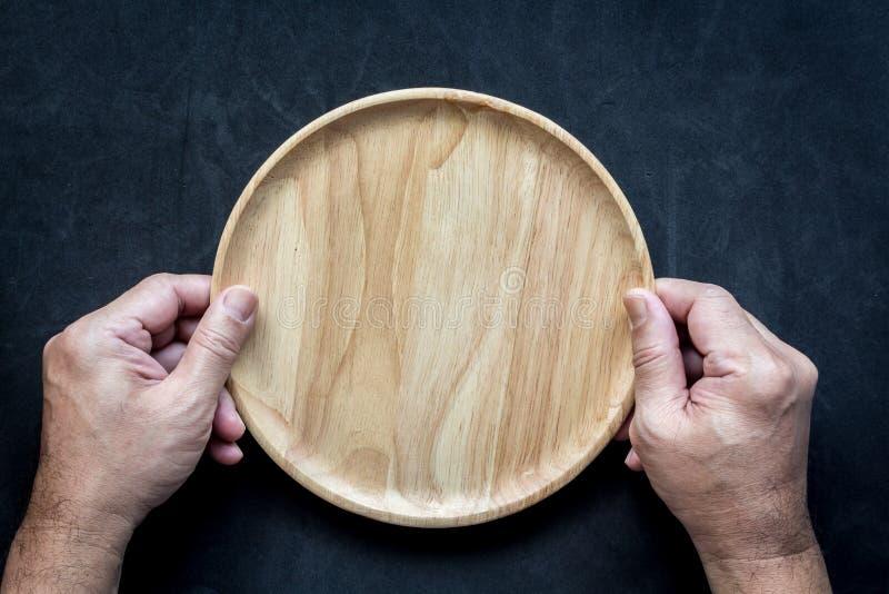 Τα χέρια ατόμων κρατούν το κενό ξύλινο πιάτο στοκ φωτογραφία με δικαίωμα ελεύθερης χρήσης