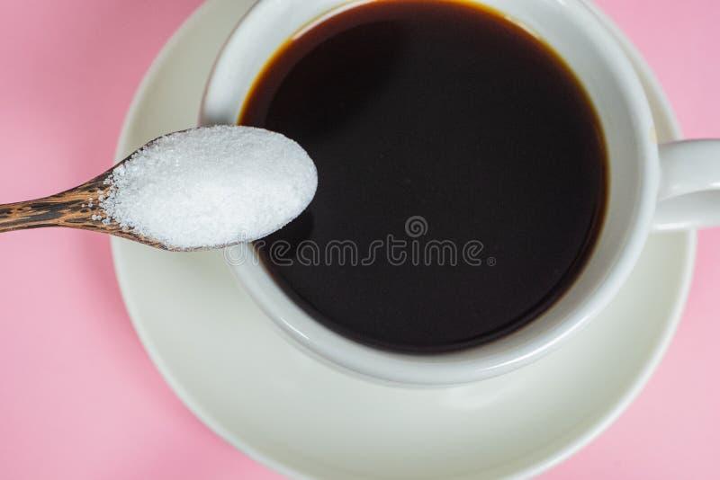 Τα χέρια γεμίζουν τη ζάχαρη στον καφέ σε ένα ρόδινο υπόβαθρο στοκ εικόνες