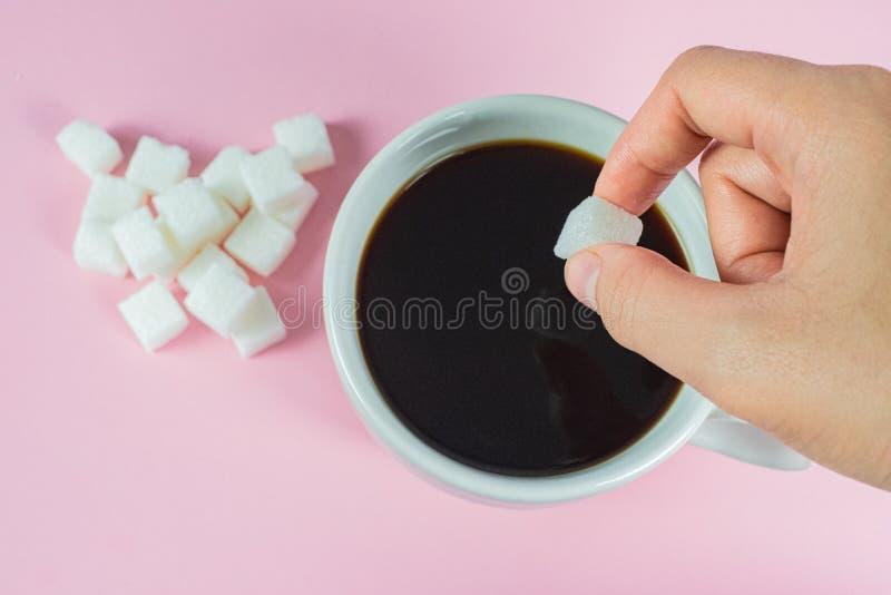Τα χέρια γεμίζουν τους κύβους ζάχαρης στον καφέ σε ένα ρόδινο υπόβαθρο στοκ εικόνες
