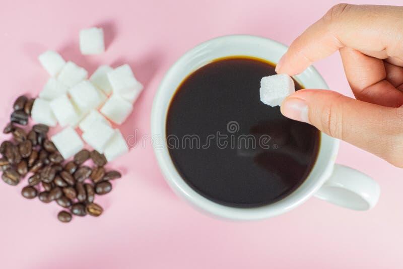 Τα χέρια γεμίζουν τους κύβους ζάχαρης στον καφέ σε ένα ρόδινο υπόβαθρο στοκ εικόνα με δικαίωμα ελεύθερης χρήσης
