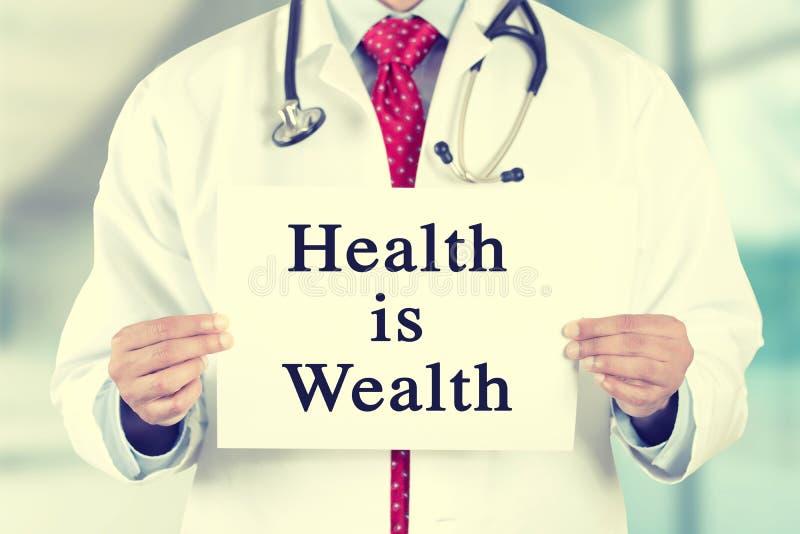Τα χέρια γιατρών που κρατούν το άσπρο σημάδι καρτών με την υγεία είναι μήνυμα κειμένου πλούτου στοκ φωτογραφία με δικαίωμα ελεύθερης χρήσης