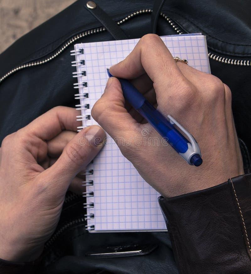 Τα χέρια γράφουν μια επιστολή Υπό εξέταση μια μάνδρα για το γράψιμο στοκ εικόνες