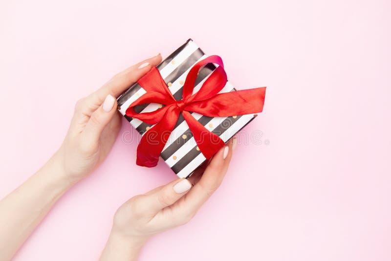 Τα χέρια γυναικών με το δώρο παρουσιάζουν το κιβώτιο στα άσπρα και μαύρα λωρίδες με ένα κόκκινο τόξο κορδελλών που απομονώνεται σ στοκ εικόνες