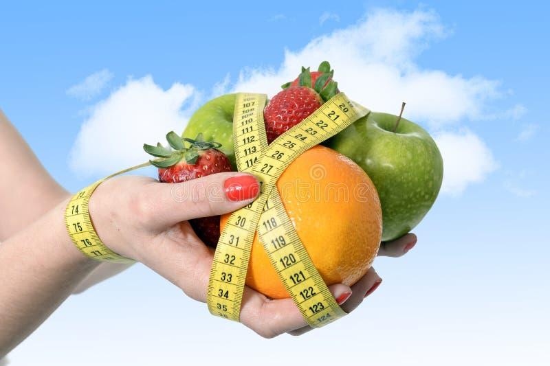 Τα χέρια γυναικών με το μίγμα των φρούτων συνδέουν τον καρπό που τυλίγεται με την ταινία μέτρου να κάνουν δίαιτα στοκ εικόνες