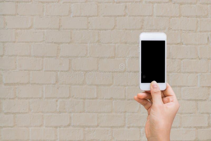 Τα χέρια γυναικών με το τηλέφωνο κυττάρων τοίχων, χλευάζουν επάνω στοκ εικόνες με δικαίωμα ελεύθερης χρήσης