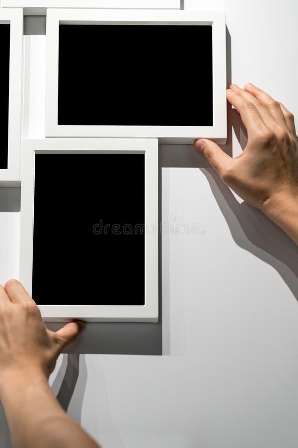 Τα χέρια γυναικών που κρατούν και που ρυθμίζουν το άσπρο πρότυπο πλαισίων φωτογραφιών κρεμούν στοκ εικόνες